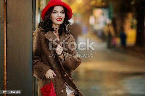518885222istockphoto Stylish woman with bright evening make-up in red gloves and a red evening hat in the city in an autumn coat 1210264645
