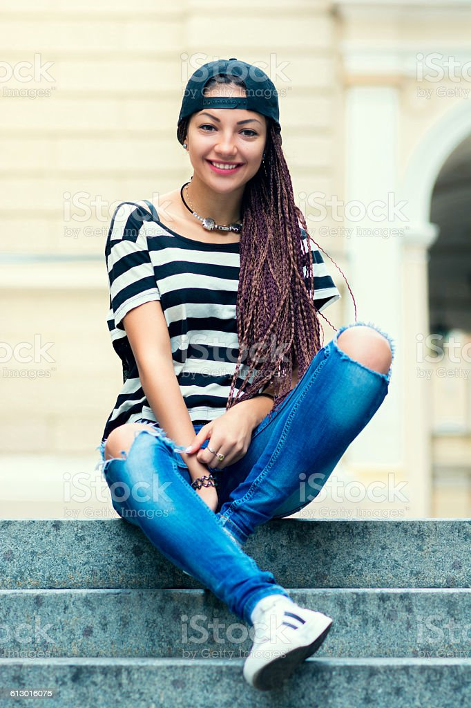 Stylish woman with dreads sitting on the stairs and smile stock photo