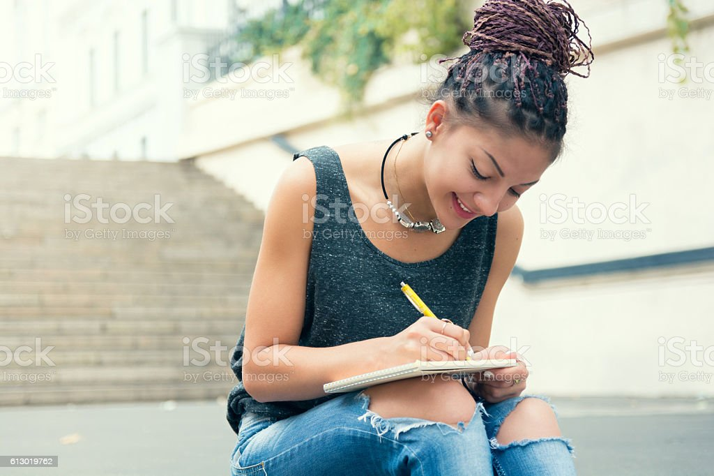 Stylish woman with dreads writting down the notes at street stock photo
