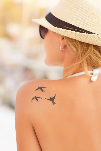 Stylische Frau mit schönem Tattoo auf der Schulter – Foto