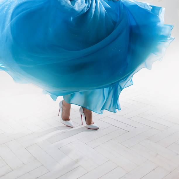 Pies de mujer con estilo en una falda hinchada y zapatos blancos. - foto de stock