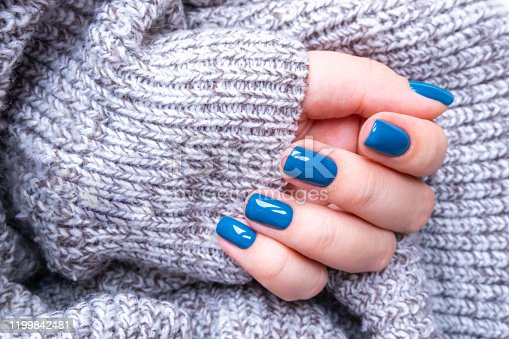 1128559926 istock photo Stylish women's manicure in blue on the background of a knitted gray jacket. The concept of self-care 1199842481