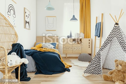 istock Stylish wooden commode in bright bedroom interior with poster on the wall 1156142608