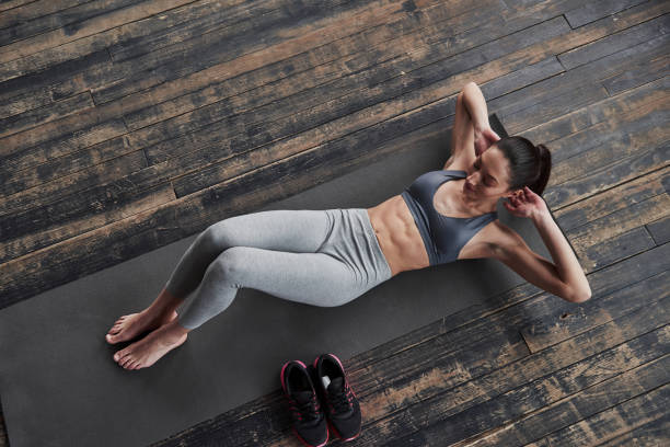 Stylish wooden floor. Top view of girl with slender body works on the abs when lying on the floor Stylish wooden floor. Top view of girl with slender body works on the abs when lying on the floor. abdominal muscle stock pictures, royalty-free photos & images