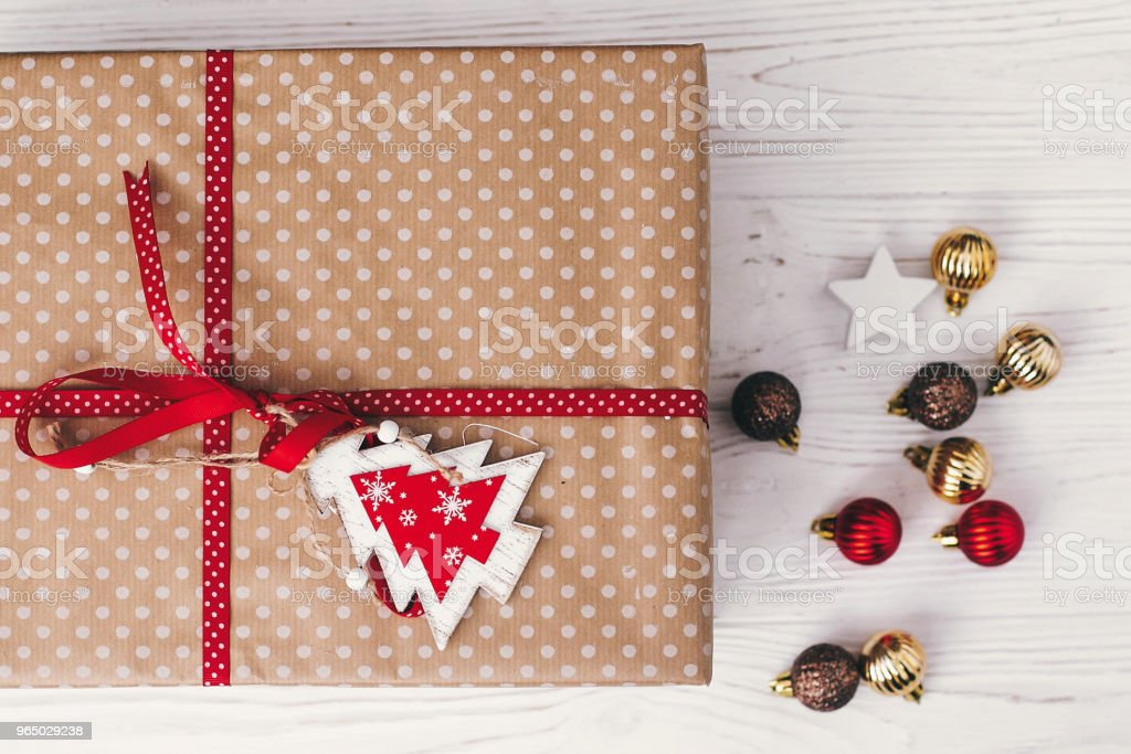 stylish wrapped gift box top view, with ornaments and  tree. present flat lay. seasonal greetings, happy holidays. merry christmas and happy new year concept royalty-free stock photo