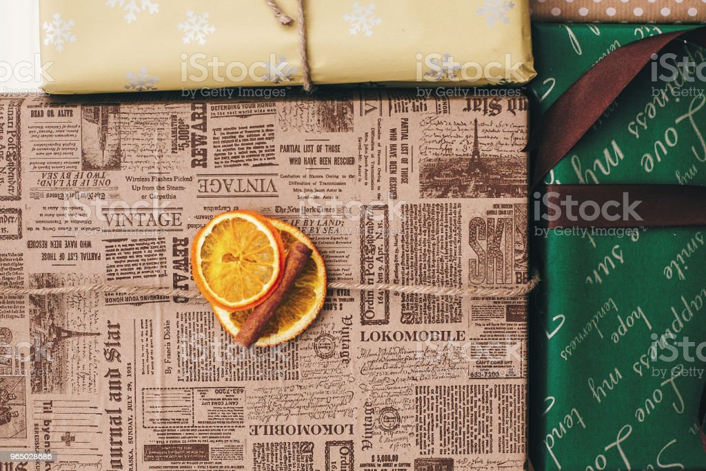 stylish wrapped gift boxes top view, with ornaments orange cinnamon and twine. merry christmas and happy new year concept. image flat lay. seasonal greetings, happy holidays royalty-free stock photo