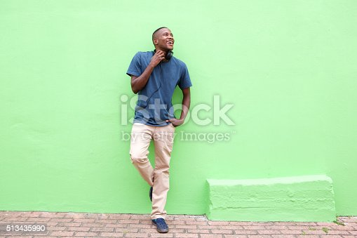 Full length portrait of stylish young african man standing against a green wall and looking away