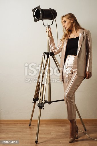 939155332 istock photo stylish young business woman in trousers and a jacket stands near a theatrical lantern 898294296