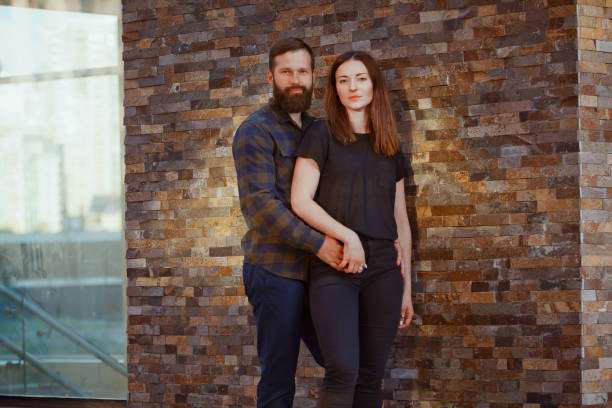 stylish young couple is spending time together outdoors. attractive woman and handsome bearded man are posing on brick background. - brunette woman eyeglasses kiss man foto e immagini stock