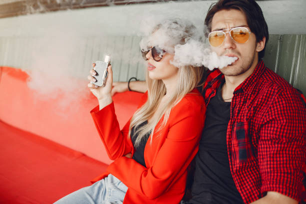 Stylish young couple with vape in a city stock photo