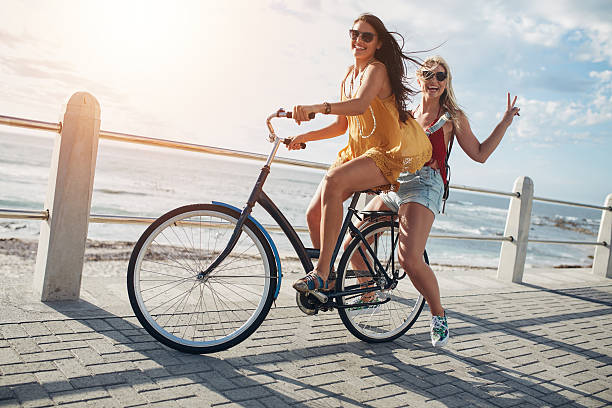 Stylish young female friends on a bicycle stock photo
