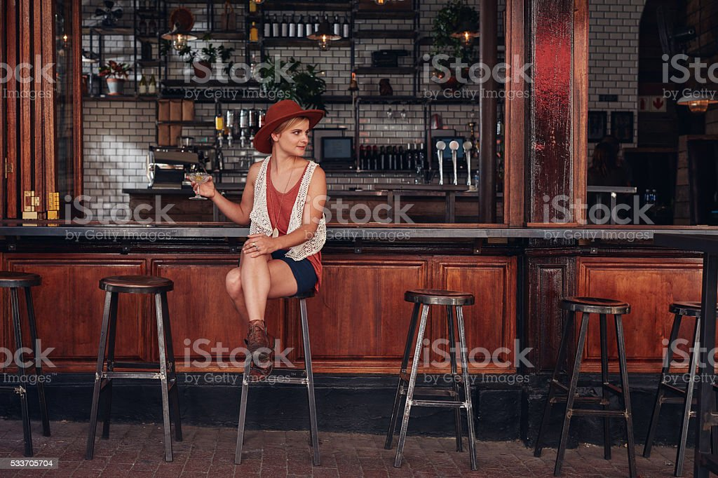 Stylish young female sitting at a cafe with drink stock photo