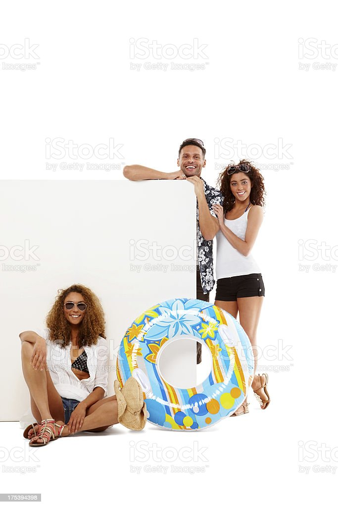 Stylish young friends on holiday with empty board stock photo
