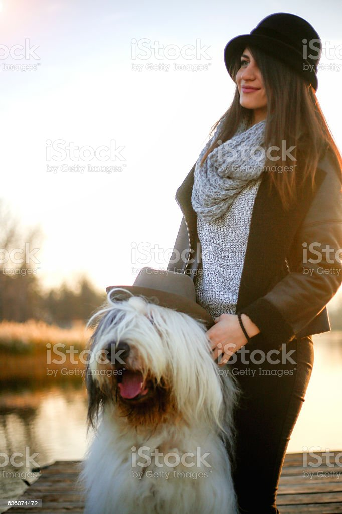 Stylish young girl and dog posing on the pier stock photo