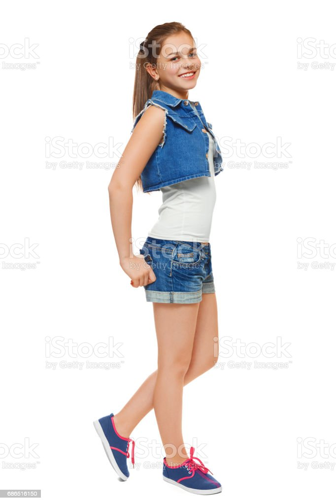 Stylish young girl in a jeans vest and denim shorts. Street style teenager, lifestyle, isolated on white background foto stock royalty-free