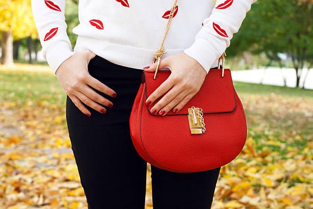 stilvolle junge mädchen mit roten handtasche. herbst-outfit - handtasche jeans stock-fotos und bilder