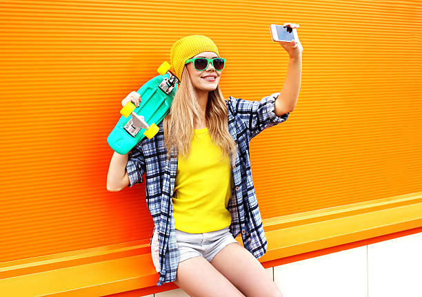 stylish young girl with skateboard makes self-portrait on smartphone stock photo