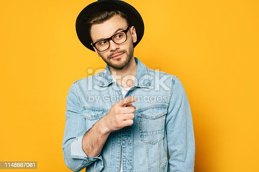 649754038 istock photo Stylish young hipster guy in glasses and hat is pointing away over yellow wall 1148667061
