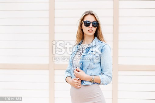 578791454istockphoto Stylish young hipster woman in black sunglasses in trendy denim blue jacket posing near a wooden vintage white building outdoors on a  summer day. Modern cute girl. 1129141651