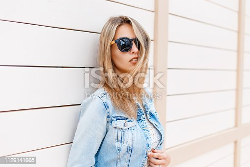 578791454istockphoto Stylish young hipster woman in black sunglasses in trendy denim blue jacket posing near a wooden vintage white building outdoors on a sunny summer day. Modern cute girl. 1129141665