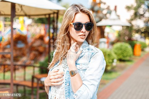 578791454istockphoto Stylish young hipster woman in trendy in sunglasses in fashionable blue summer denim jacket in vintage white lace blouse on a walk in an amusement park. Charming girl enjoys the weekend. Lifestyle. 1129141470