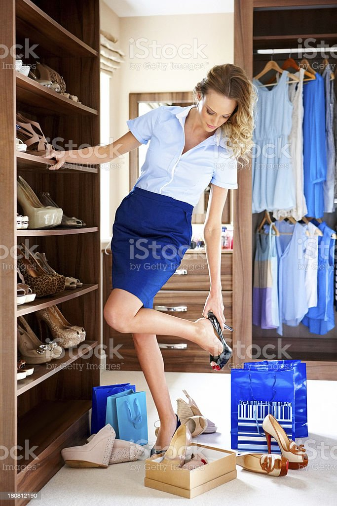 Stylish young lady choosing shoes to wear stock photo
