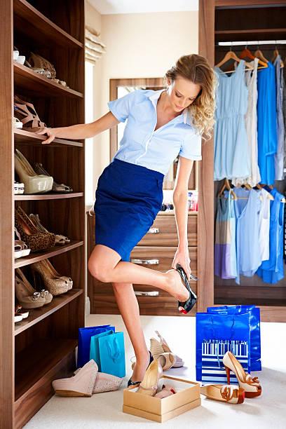 stilvolle junge frau auswahl schuhe zu tragen. - garderobe mit schuhschrank stock-fotos und bilder