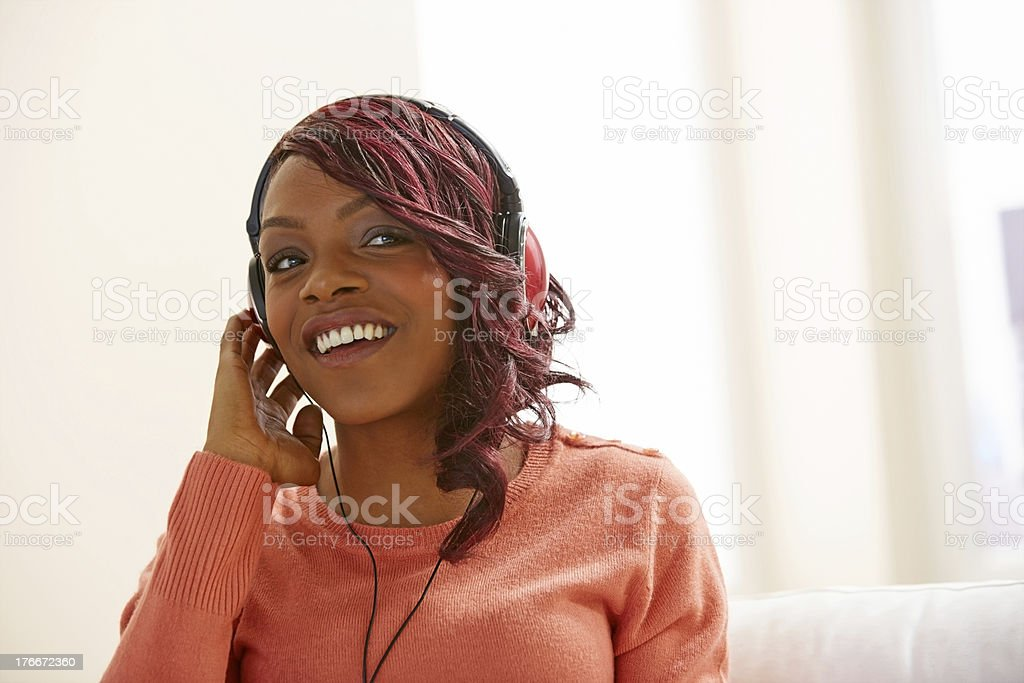 Stylish young lady listening to music on headphone royalty-free stock photo