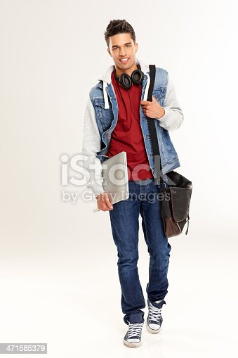 Full length portrait of stylish young man going to college with laptop in hand over white background