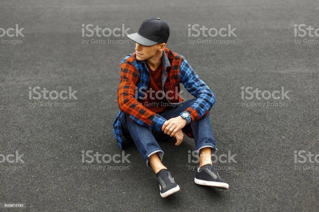 Stylish young man in a black cap, shirt, jeans and sneakers sits on the pavement. stock photo