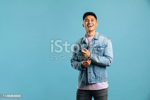 A young man standing alone in a studio with a blue backdrop, looking towards the camera and smiling.