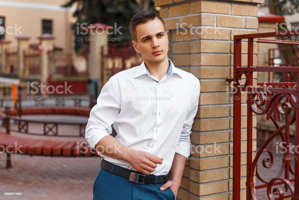 Stylish young man in a white shirt near a brick wall stock photo