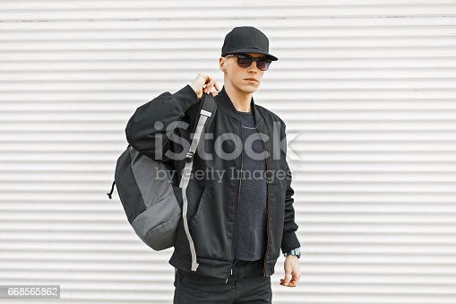 istock Stylish young man in black modern clothes with a backpack near a white wall 668565862
