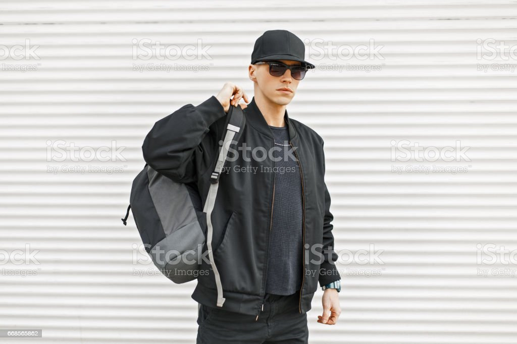 Stylish young man in black modern clothes with a backpack near a white wall stock photo