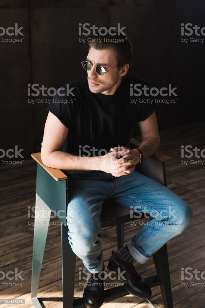 stylish young man in black t-shirt and sunglasses sitting on chair royalty-free stock photo