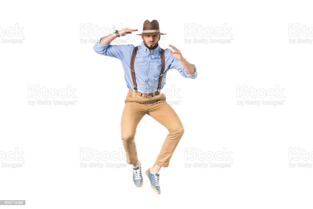 élégant jeune homme au chapeau sautant et regardant la caméra isolé sur blanc - Photo