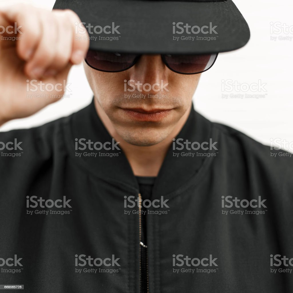 Stylish young man in sunglasses and a black cap stock photo