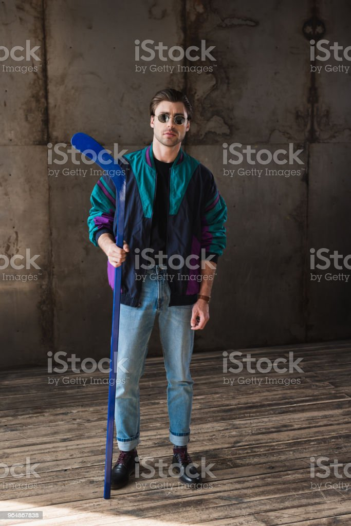 stylish young man in vintage windcheater and sunglasses with hockey stick looking at camera royalty-free stock photo