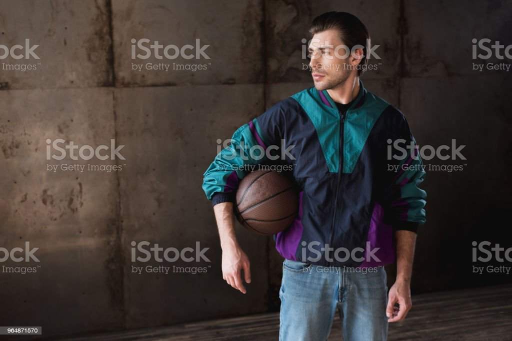 stylish young man in vintage windcheater with basketball ball looking away royalty-free stock photo
