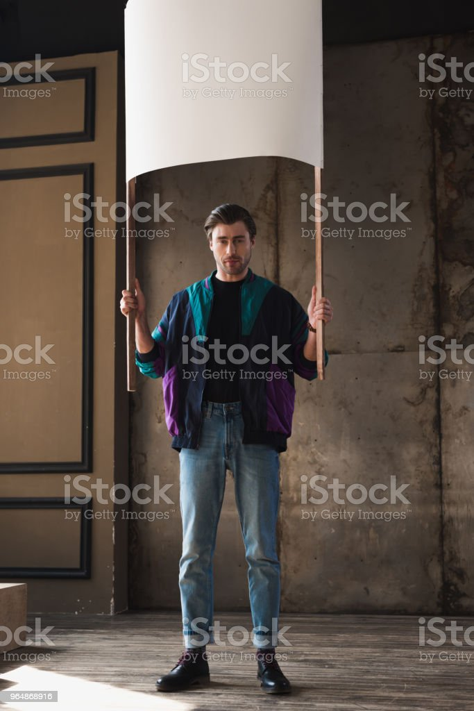stylish young man in vintage windcheater with blank placard royalty-free stock photo