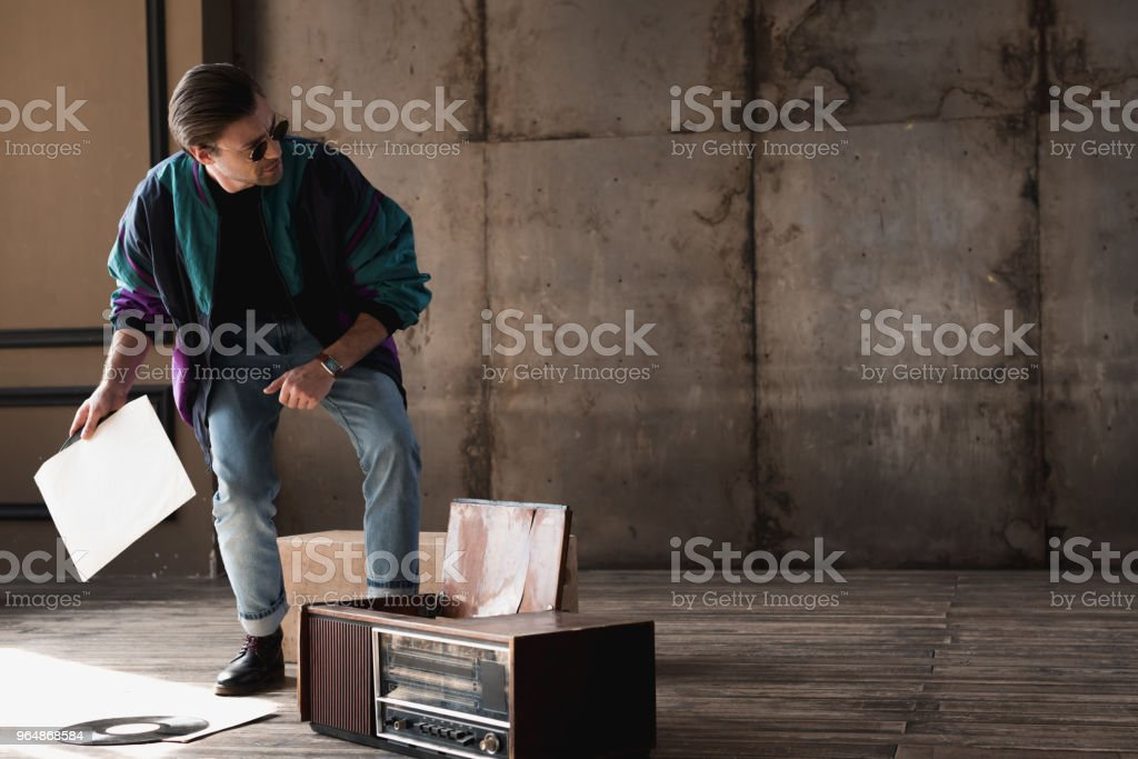 stylish young man in vintage windcheater with vinyl record player royalty-free stock photo