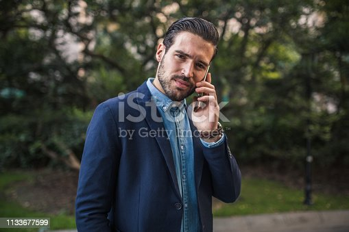 One young modern man is walking in the park and talking on mobile phone