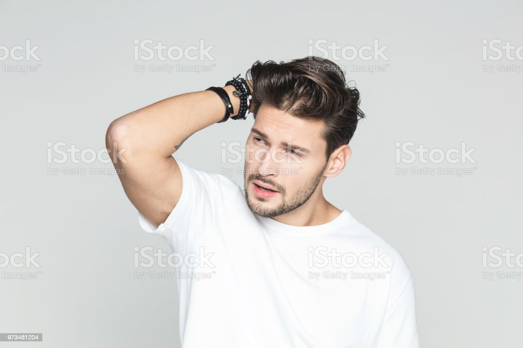 Stylish young man Portrait of good looking young man posing with hand in hair against grey background. 25-29 Years Stock Photo
