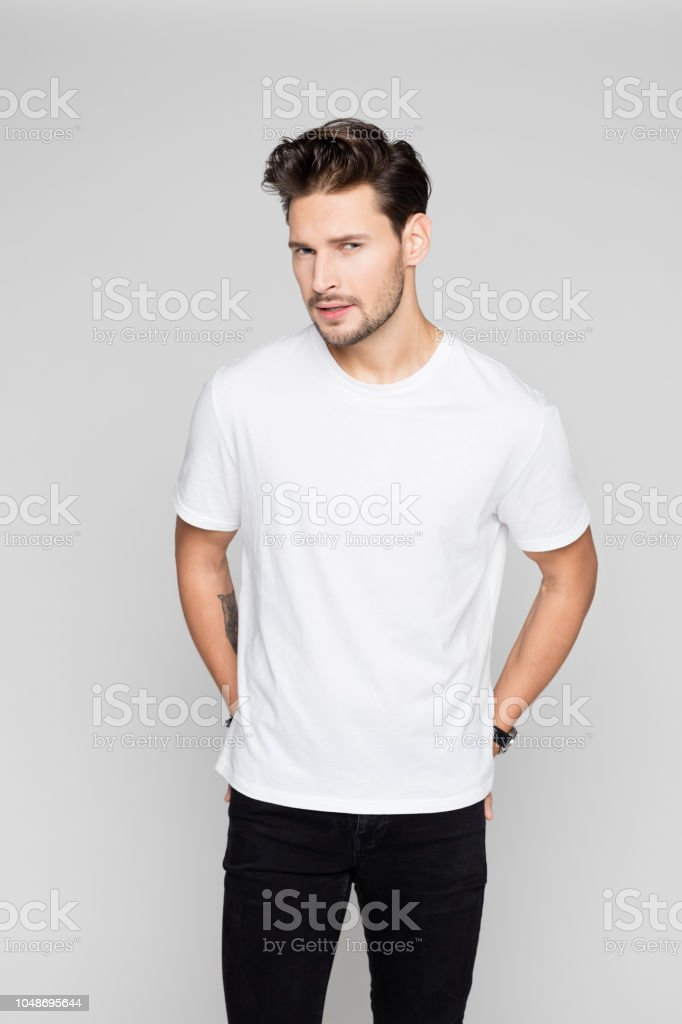 Stylish young man posing on grey background Portrait of stylish young man posing on grey background and looking at camera 25-29 Years Stock Photo
