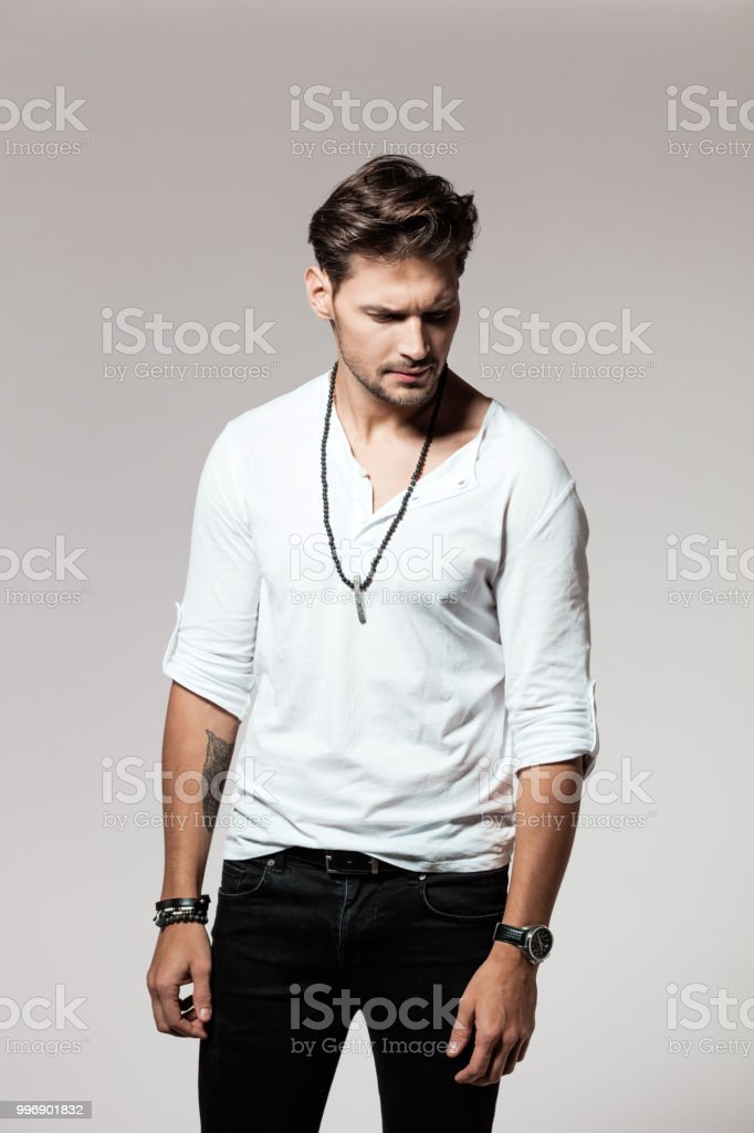 Stylish young man standing on grey background Studio portrait of stylish young man standing on grey background 25-29 Years Stock Photo