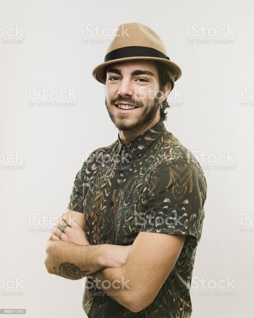 Stylish young man standing with his arms crossed stock photo