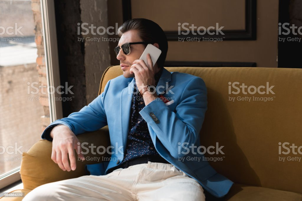 stylish young man talking by phone while sitting on couch royalty-free stock photo