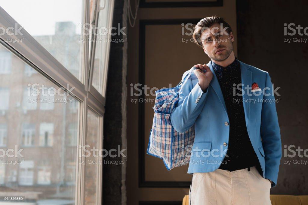 時尚的年輕男子與老式拉鍊行李袋肩上 - 免版稅一個人圖庫照片