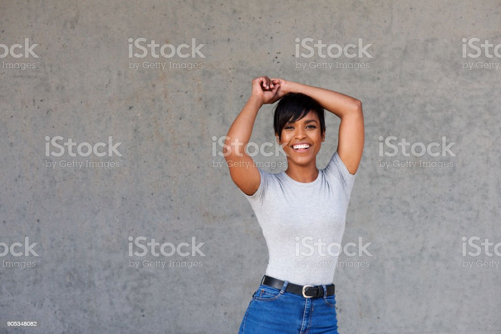 Stylish young modern black woman standing against gray wall stock photo