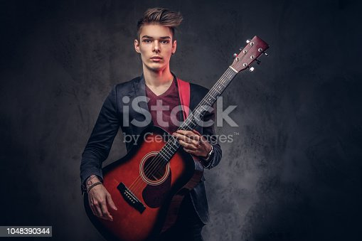 istock Stylish young musician with stylish hair in elegant clothes, playing on an acoustic guitar. 1048390344